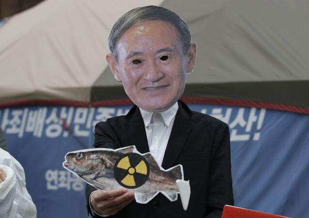 Manifestante em máscara do premiêr japonês, Yoshihide Suga, durante o protesto contra despejo de água contaminada da usina nuclear de Fukushima, 13 de abril de 2021