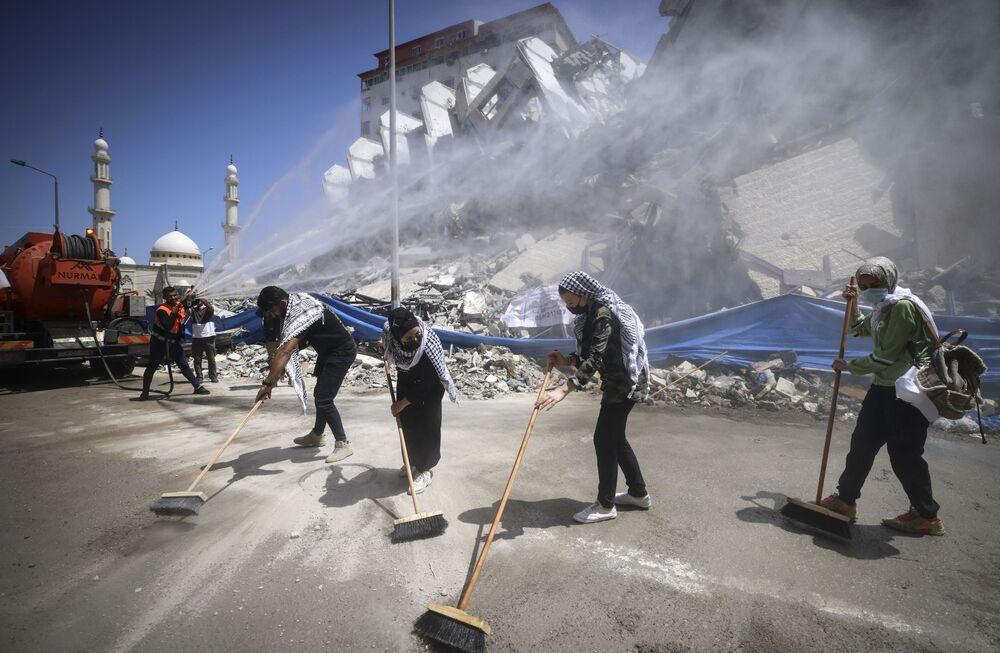 Voluntários e trabalhadores municipais palestinos limpam os escombros do complexo Hanadi, destruído por um ataque aéreo israelense, na Faixa de Gaza, 25 de maio de 2021