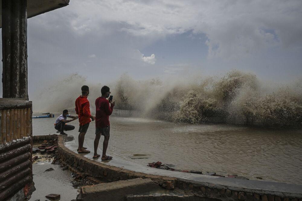 Residentes tiram fotos das ondas durante o ciclone Yaas que atingiu a costa leste da Índia, 27 de maio de 2021