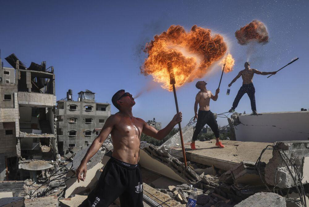 Membros da equipe esportiva palestina Bar Woolf fazem exibição sobre ruínas, após um ataque aéreo israelense, em Beit Lahia, Faixa de Gaza, 26 de maio de 2021