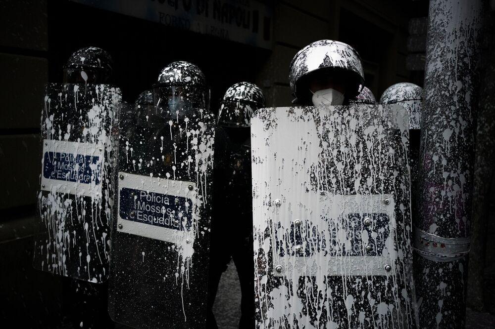 Agentes da polícia de choque cobertos com tinta jogada por manifestantes ficam de guarda enquanto ativistas tentam impedir a expulsão de Axel Altadill, de 29 anos, de um apartamento em Barcelona, Espanha, 25 de maio de 2021. Altadill é acusado de ocupar ilegalmente o apartamento desde janeiro de 2019