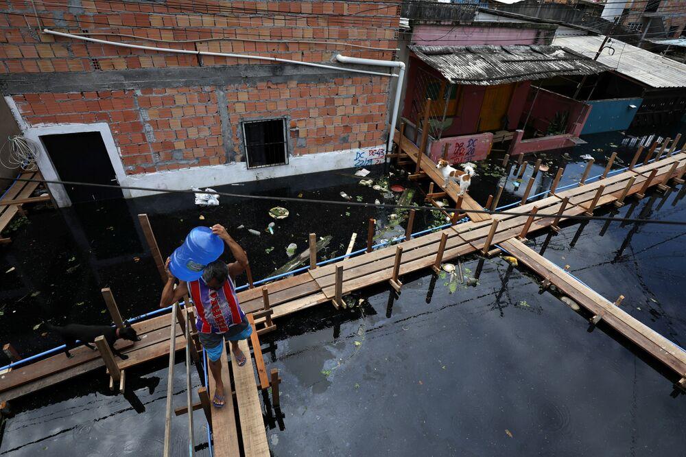 Homem transporta água potável por rua inundada após transbordamento do rio Negro, Manaus, Amazonas, Brasil, 28 de maio de 2021