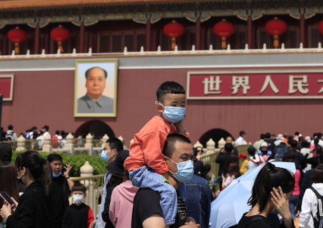 Homem carrega criança nas costas perto da Porta de Tiananmen em Pequim com retrato de Mao Tsé-tung ao fundo