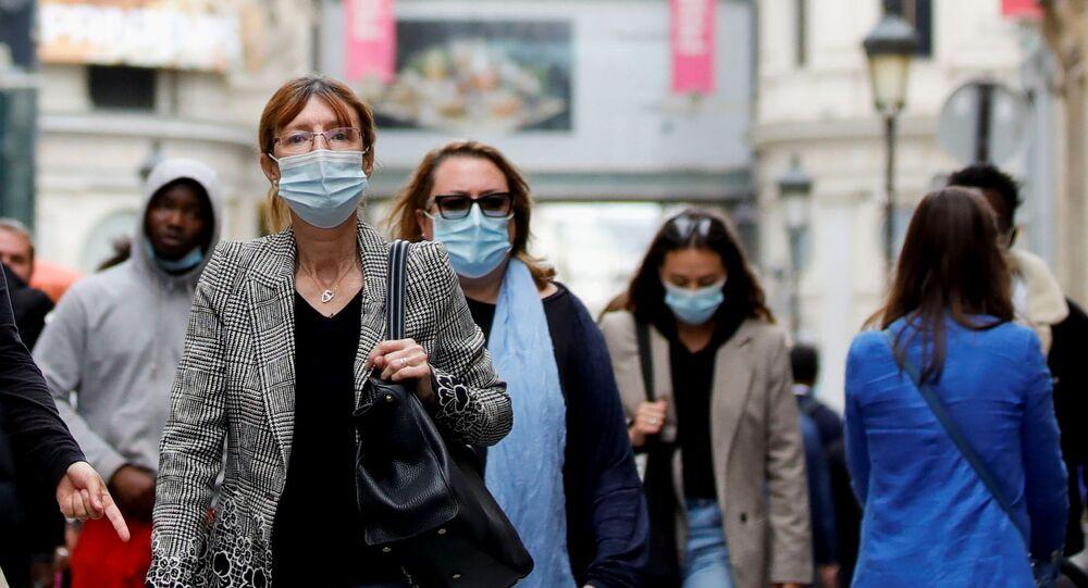 Pessoas usando máscaras de proteção caminham por rua em Paris, França, 27 de maio de 2021