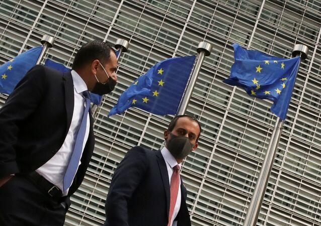 Pessoas passam por bandeiras da União Europeia içadas na sede da Comissão Europeia em Bruxelas, Bélgica, 5 de maio de 2021
