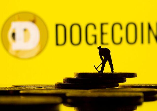 Pequena figura de brinquedo em representação de criptomoeda com o logotipo da Dogecoin no fundo, em 20 de abril de 2021