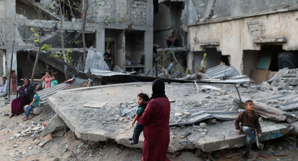 Uma mulher palestina carrega uma criança perto de casas destruídas durante o conflito israelense-palestino, no norte da Faixa de Gaza em 1º de junho de 2021