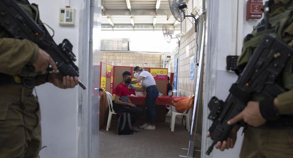 Soldados israelenses montam guarda enquanto um palestino que trabalha em Israel recebe uma vacina Moderna COVID-19 no cruzamento Tarkumiya entre a Cisjordânia e Israel, segunda-feira, 8 de março de 2021