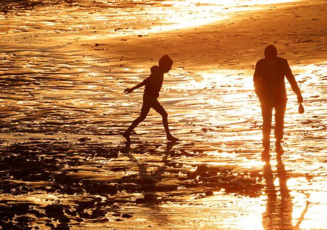 Menino e pai desfrutam do pôr do sol na praia, em meio à disseminação da doença do novo coronavírus (COVID-19) em Cayeux-sur-Mer, França, 29 de maio de 2021