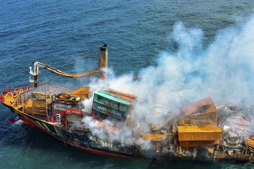 Fumaça sai do navio MV X-Press Pearl, carregado com centenas de contêineres de produtos químicos e plásticos, enquanto é rebocado para longe da costa de Colombo, Sri Lanka