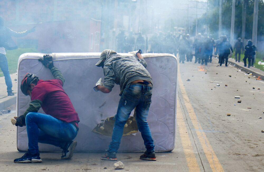 Manifestantes se escondem atrás de um colchão durante confrontos com a polícia de choque na Colômbia