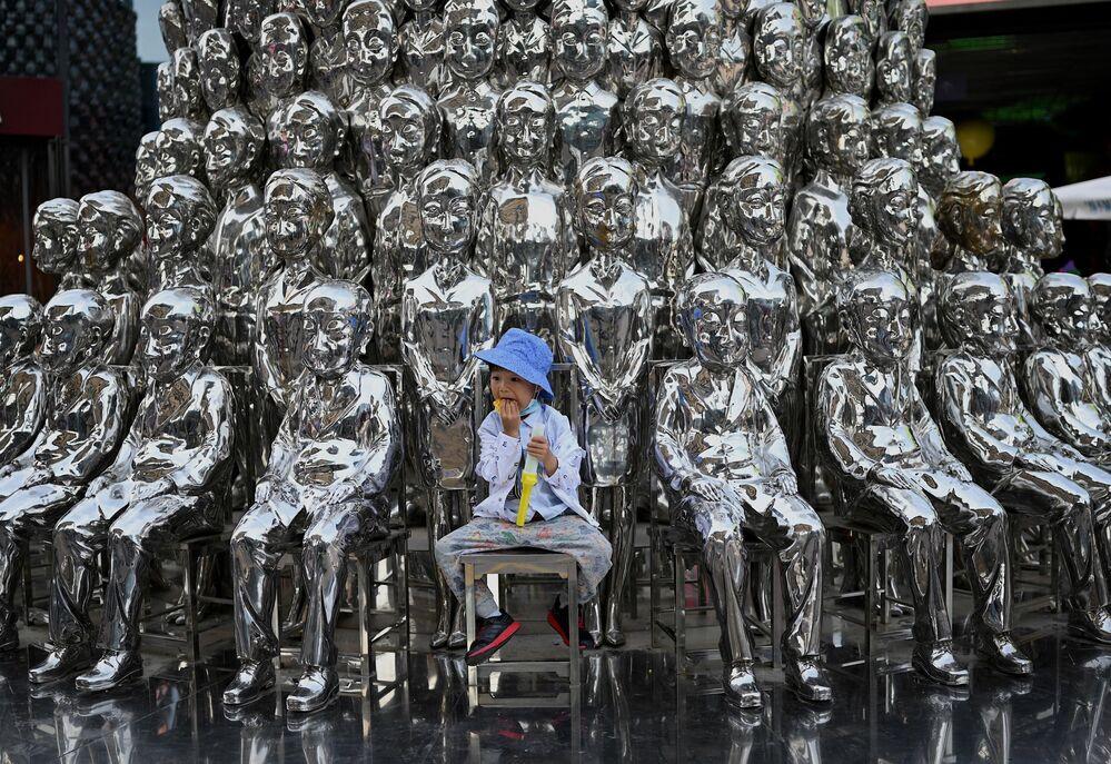 Menino sentado entre várias esculturas expostas em um centro comercial de Pequim, na China