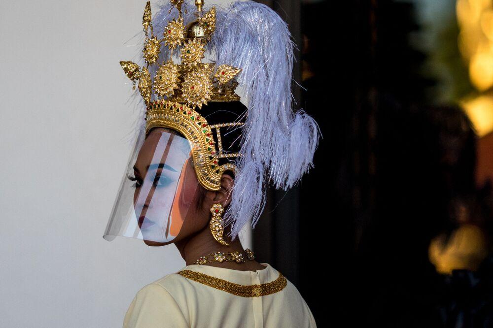 Dançarina tailandesa com um ornamento tradicional e uma proteção contra o coronavírus