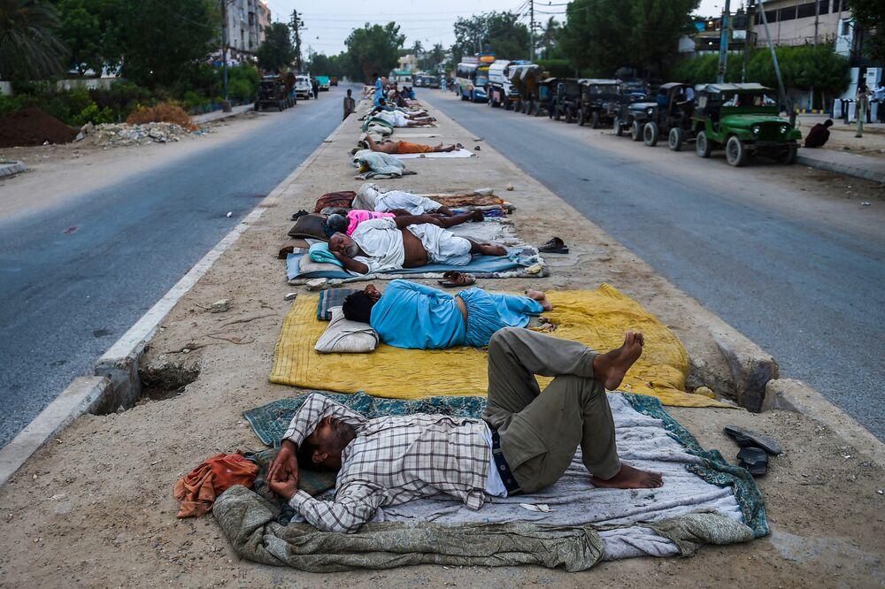 Trabalhadores dormindo na faixa divisória em rodovia da cidade portuária de Karachi, Paquistão