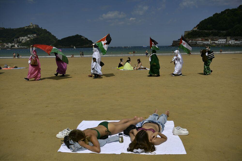 Manifestantes sarauís agitam bandeiras na praia de San Sebastián, na Espanha