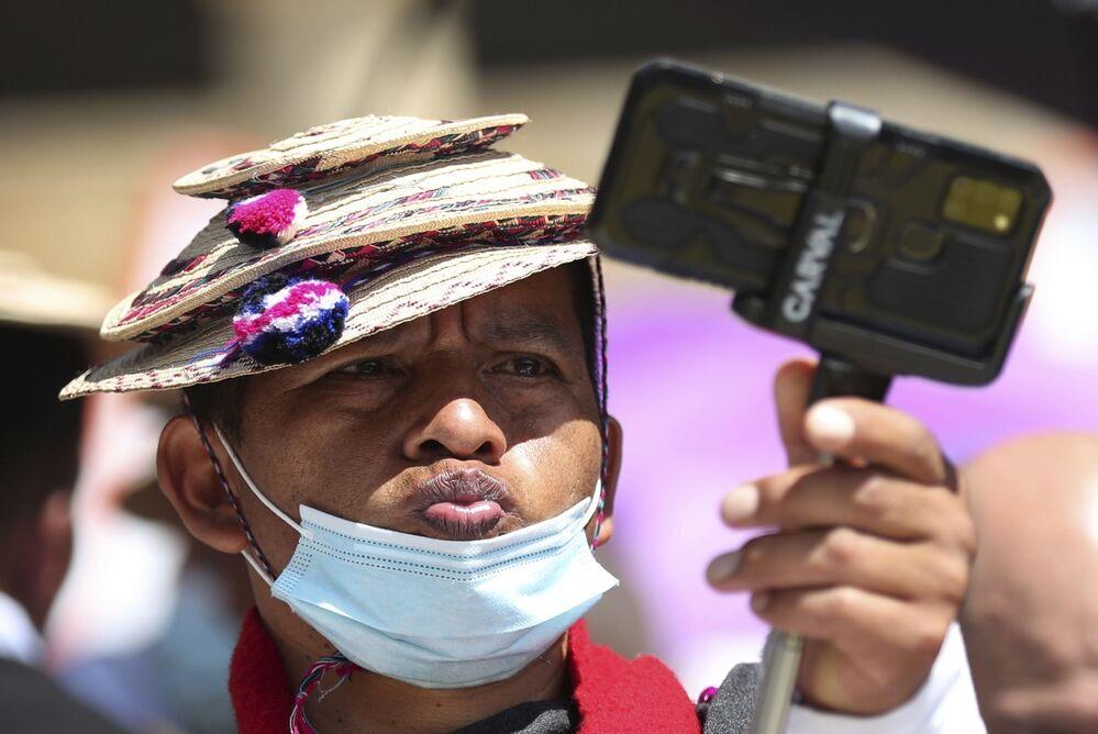 Homem do povo indígena Misak tira selfie durante um protesto antigovernamental em Bogotá, Colômbia
