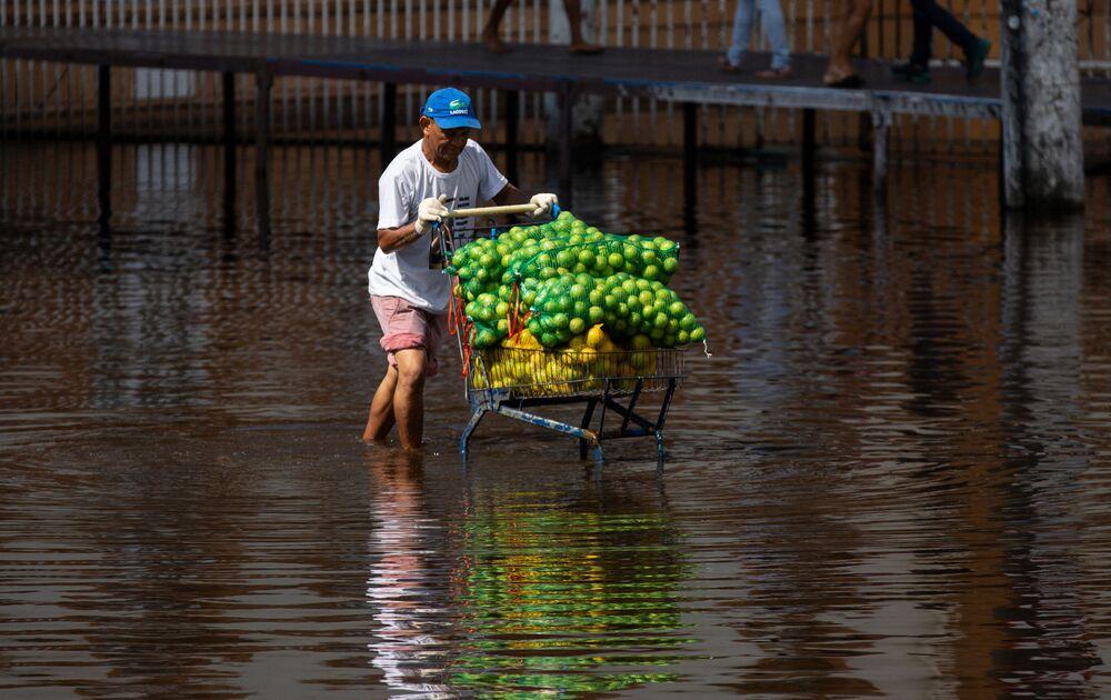 Homem empurra um carrinho de frutas por uma rua alagada no centro de Manaus