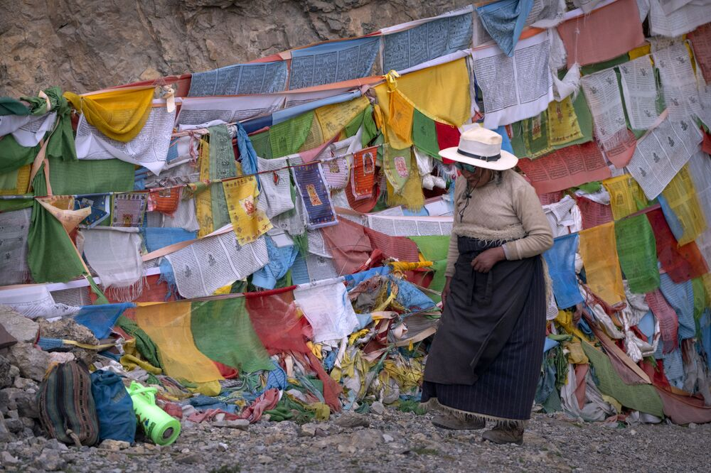 Mulher passa por bandeiras de oração em um templo budista em Namtso, Tibete