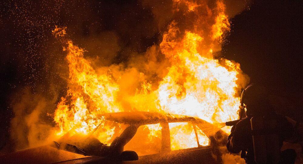 Carro incendiado com fogo sendo apagado por bombeiro