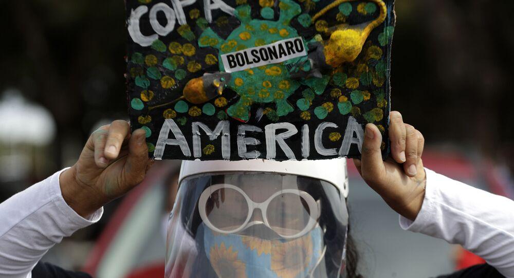 Mulher segura cartaz de protesto contra a organização da Copa América pelo Brasil, 6 de junho de 2021
