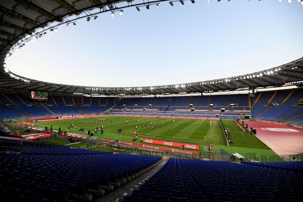 Vista geral do Estádio Olímpico em Roma, Itália, 17 de junho de 2020, durante o aquecimento de jogadores, quando o jogo recomeça a portas fechadas após o surto da pandemia da COVID-19
