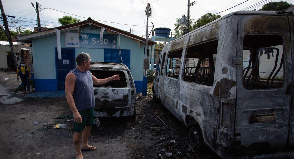 Homem olha para veículos queimados após onda de ataques violentos em Manaus, estado do Amazonas, 7 de junho de 2021