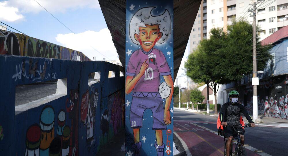 Homem anda de bicicleta perto de grafite que representa um jogador de futebol, em São Paulo, Brasil, 1º de junho de 2021