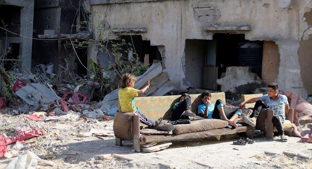 Crianças palestinas sentadas junto a escombros de casas destruídas durante ataques aéreos de Israel em maio, em Gaza, 9 de junho de 2021