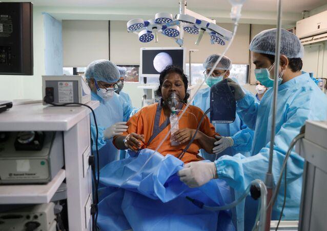 O dr. Brajpal Singh Tyagi, está ao lado de Usha Arya, 56, que sofre de mucormicose, também conhecida como fungo negro, após realizar uma cirurgia endoscópica nos seios da face no hospital Harsh ENT em Ghaziabad, nos arredores de Nova Deli, Índia 31 de maio, 2021