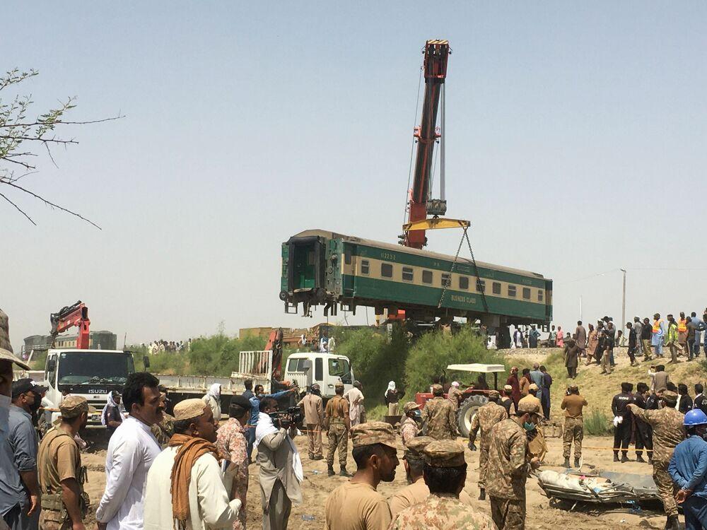 Soldados e residentes no local de um acidente ferroviário, enquanto funcionários retiram vagão do local de colisão entre dois trens em Ghotki, Paquistão, 7 de junho de 2021
