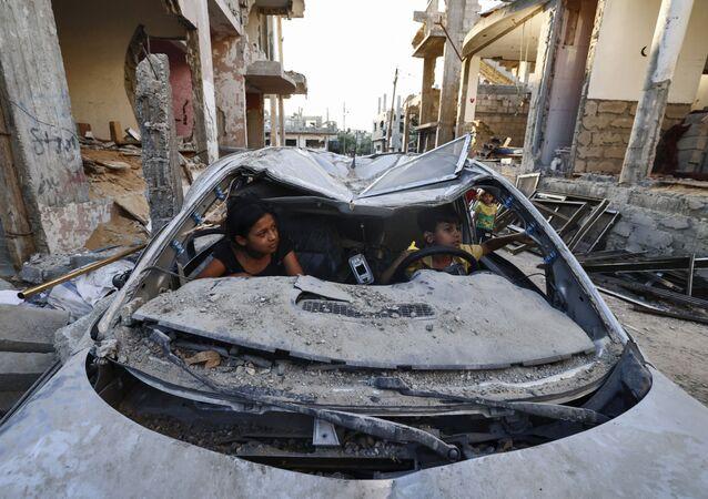 Crianças palestinas brincam dentro de carro destruído durante conflito entre o Hamas e Israel, em Beit Hanun, Faixa de Gaza, 7 de junho de 2021