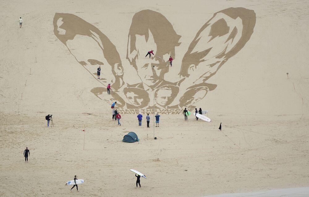 Surfistas e banhistas observam os toques finais nos desenhos dos líderes do G7 na praia de Newquay, Cornualha, Reino Unido, 10 de junho de 2021