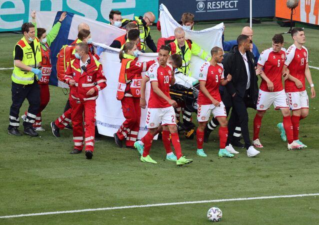 Jogadores da Dinamarca se reúnem enquanto paramédicos assistem o meio-campista Christian Eriksen (fora da foto) durante a partida de futebol do Grupo B do UEFA EURO 2020 entre a Dinamarca e a Finlândia, no Estádio Parken em Copenhague, Dinamarca, 12 de junho de 2021
