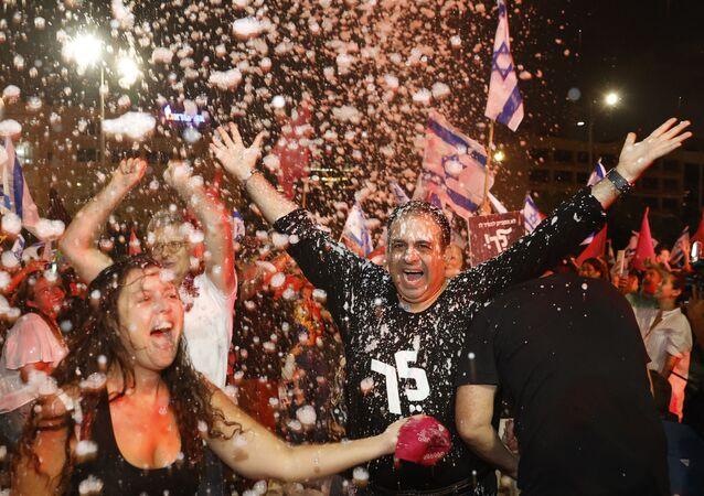 Manifestantes celebram votação no Knesset de Israel que confirmou o novo governo de coalizão israelense, Tel Aviv, 13 de junho de 2021
