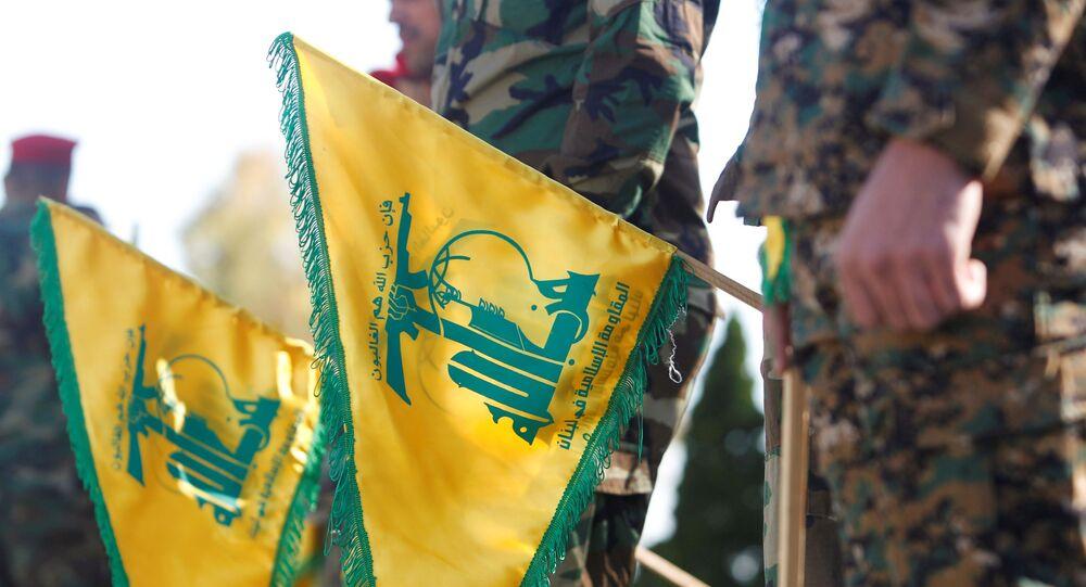 Membros do Hezbollah seguram bandeiras durante o Dia da Resistência e Libertação libanês no sul do Líbano, 25 de maio de 2021