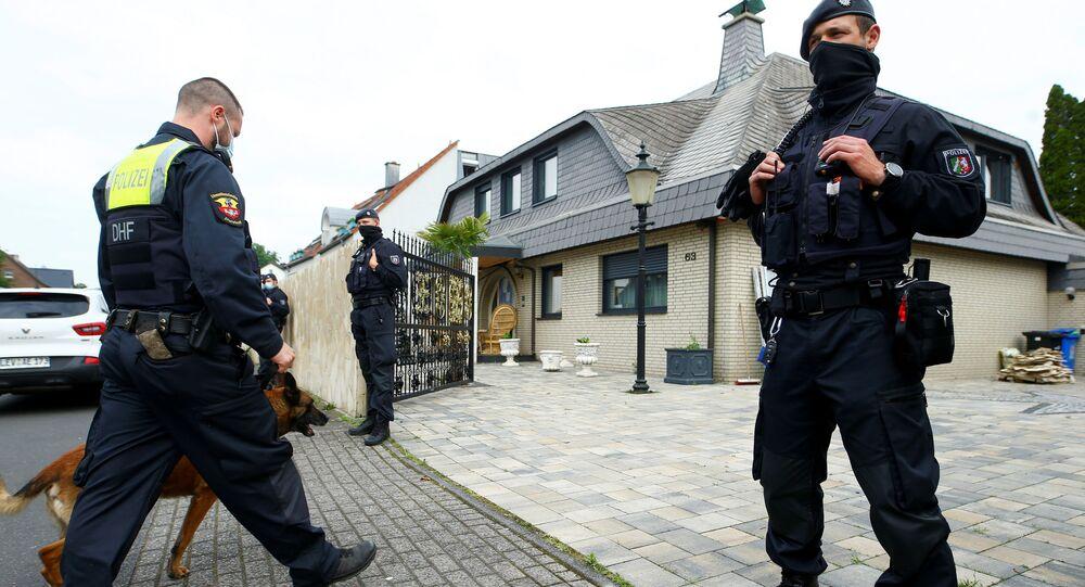 Policiais alemães e cão farejador entram no pátio de uma residência em Leverkusen, Alemanha, 8 de junho de 2021