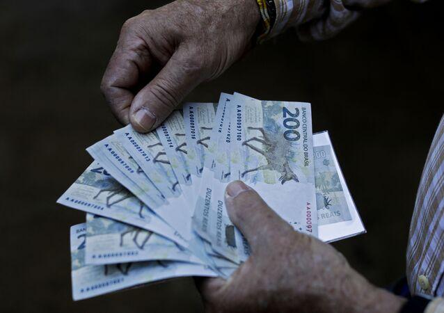 Homem segura notas de 200 reais, 2 de setembro de 2020