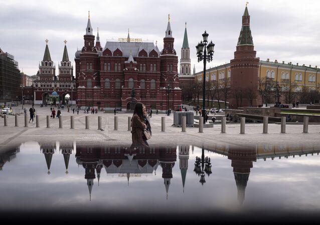 Pessoas caminham pela praça Manezh, com o Muro do Kremlin e o Museu de História ao fundo, em Moscou, Rússia, 19 de abril de 2021