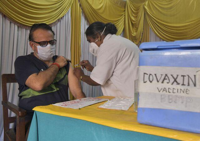 Homem é inoculado com uma dose da vacina Covaxin contra o novo coronavírus na Índia. Foto de arquivo.