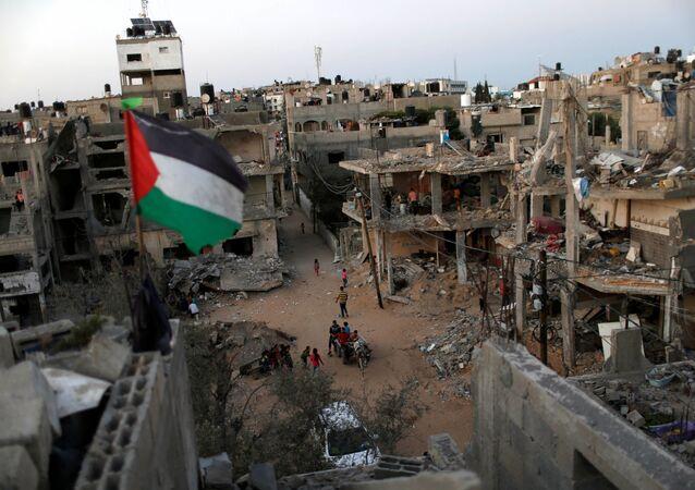 Bandeira palestina voa em meio às ruínas de casas, destruídas por ataques aéreos israelenses durante conflito israelo-palestino na Faixa de Gaza, 25 de maio de 2021