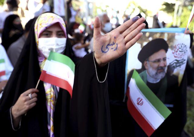 Apoiadora do candidato a presidente Ebrahim Raisi mostra inscrição em persa de seu nome, Raisi, durante manifestação em Teerã, Irã, antes da eleição presidencial, 16 de junho de 2021