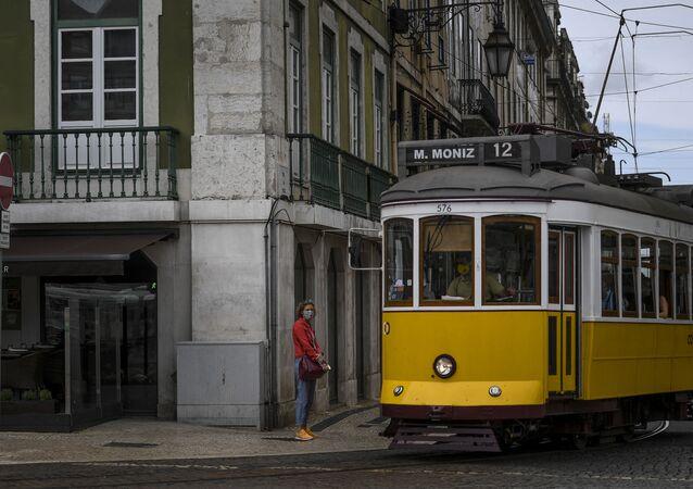 Elétrico passa por uma mulher com máscara na Baixa de Lisboa