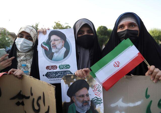 Apoiantes do candidato presidencial Ebrahim Raisi seguram cartazes com a sua fotografia durante comício eleitoral em Teerã