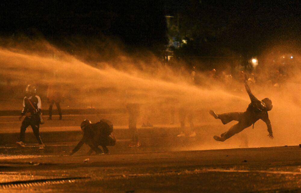 Manifestante cai após ser atingido por canhão de água durante confrontos com a polícia de choque, em meio aos protestos contra o governo do presidente colombiano Iván Duque, em Bogotá, Colômbia, 12 de junho de 2021
