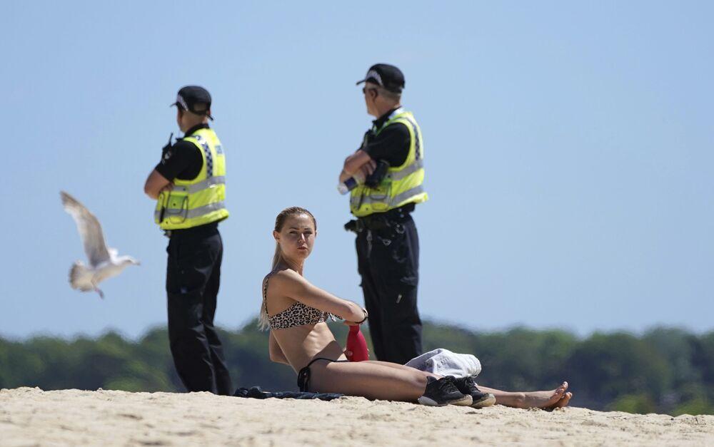 Mulher toma banho de sol, enquanto policiais patrulham as proximidades da cúpula do grupo G7 em St. Ives, Cornualha, Reino Unido, 12 de junho de 2021