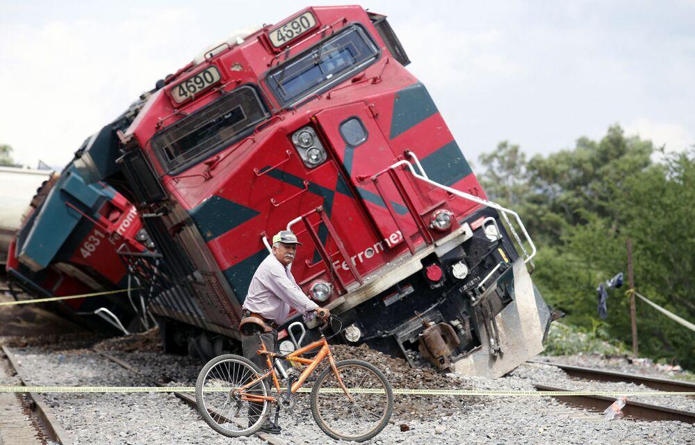 Homem com bicicleta passa junto de trem que descarrilou em Tala, estado de Jalisco, México, 15 de junho de 2021