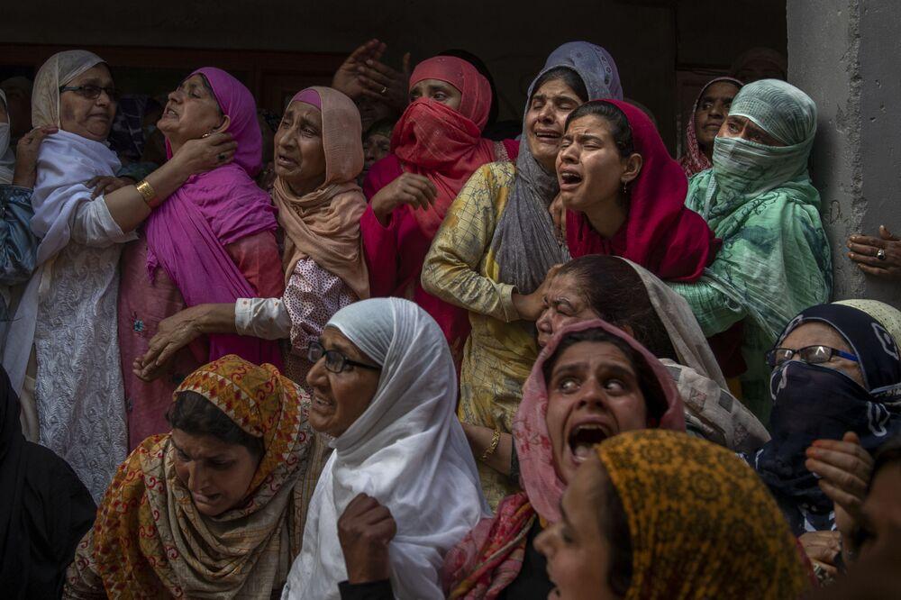 Mulheres choram durante funeral de Waseem Ahmed, policial morto em tiroteio na periferia de Srinagar, Caxemira, controlada pela Índia, 13 de junho de 2021