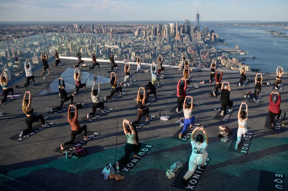 Praticantes de ioga participam de aula no Convés de Observação de Bordo, com vista para o horizonte de Manhattan, Nova York, EUA, 17 de junho de 2021