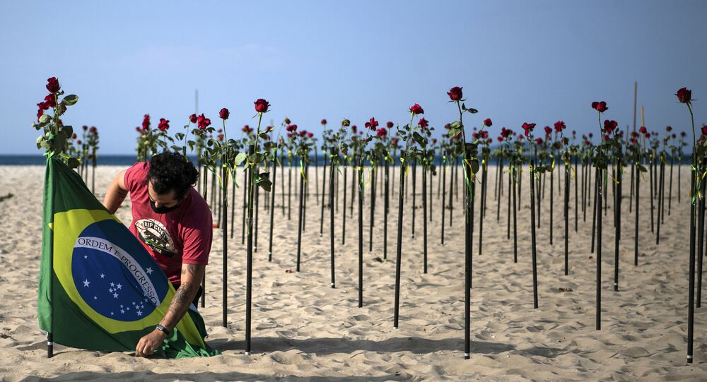 Manifestante coloca bandeira brasileira ao lado das rosas depostas pela ONG Rio de Paz na praia de Copacabana em homenagem a mais de meio milhão de mortes pela COVID-19 no país, 20 de junho de 2021