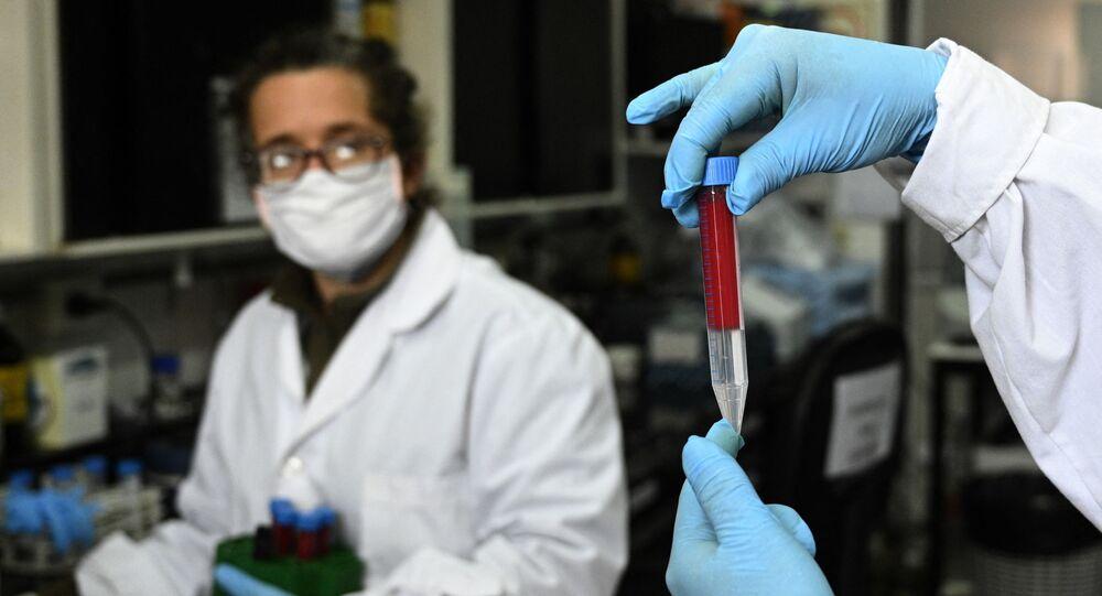Pesquisadora Viviana Parreno segura uma amostra de sangue ao lado da também pesquisadora Gisela Marcoppido em Buenos Aires, Argentina. Foto de arquivo